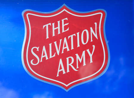 The Salvation Army shield against a blue background to the rear at the National Memorial Arboretum, Alrewas, Staffordshire, England, UK, Western Europe.