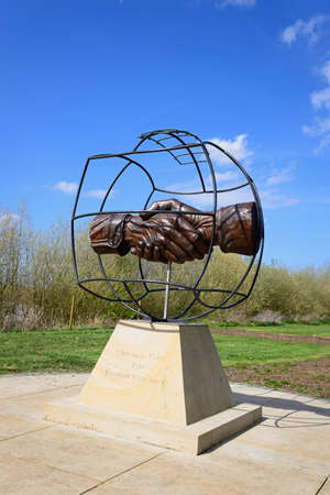 Christmas Truce Memorial showing soldiers handshake within a globe, National Memorial Arboretum, Alrewas, Staffordshire, England, UK, Western Europe.