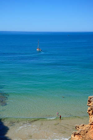Elevated view of tourists cooling down in the sea with a yacht to the rear, Praia da Rocha, Algarve, Portugal, Europe. Stock Photo