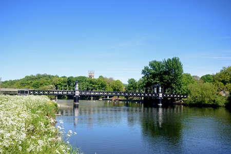 Blick auf die Ferry Bridge, auch bekannt als Stapenhill Ferry Bridge und den Fluss Trent, mit Kuhpetersilie im Vordergrund, Burton upon Trent, Staffordshire, England, Großbritannien, Westeuropa. Standard-Bild