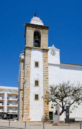 View of the mother church (Matriz de Nossa Senhora do Rosario) bell tower in the old town, Olhau, Algarve, Portugal, Europe. 報道画像