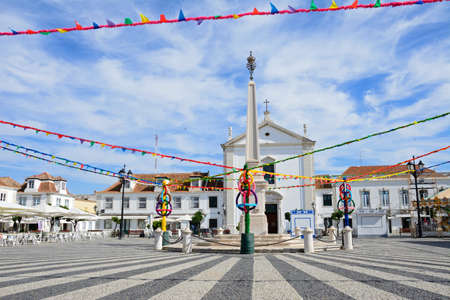 Festival streamers around the cenotaph in the Marquis of Pombal Square (Praca do Marques de Pombal) with a cenotaph and the church to the rear, Vila Real de Santo Antonio, Algarve, Portugal, Europe. Sajtókép