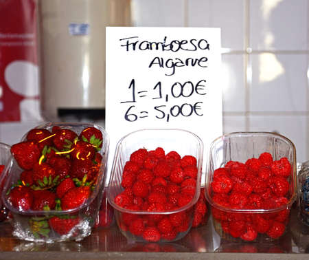 Punnets of raspberries and strawberries for sale in the indoor market, Olhau, Algarve, Portugal, Europe.