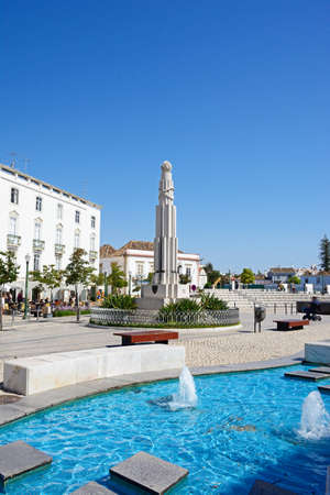 France Africa war memorial in the Praca de Republica with pavement cafes to the rear and a fountain in the foreground, Tavira, Algarve, Portugal, Europe.