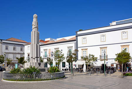 View of the France Africa war memorial in the Praca de Republica with pavement cafes to the rear, Tavira, Algarve, Portugal, Europe. Sajtókép