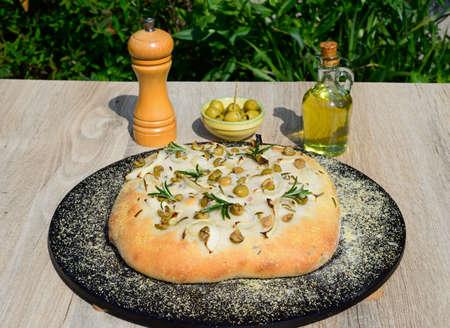 Homemade Italian rosemary, green olive and onion Focaccia bread on a baking stone, England, UK, Europe.