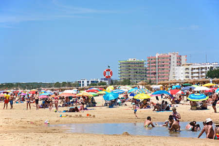 Tourists relaxing on the beach during the Summertime with hotels to the rear, Praia da Monte Gordo, Vila Real de Santo Antonio, Algarve, Portugal, Europe.