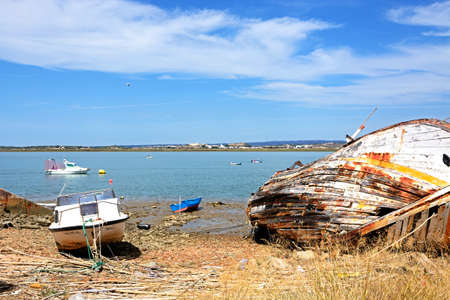 Old wooden fishing boat ruin on the riverbank with views across the River Guadiana towards Castro Marim in Portugal, Ayamonte, Huelva Province, Andalucia, Spain, Europe.