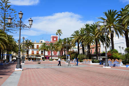 View of Coronation Square (Plaza de la Coronacion) with people passing by and a dog carrying a ball in his mouth, Ayamonte, Huelva Province, Andalucia, Spain, Europe. Éditoriale