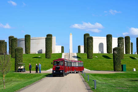 Front view of the Armed Forces Memorial with a red land train in the foreground and people enjoying the setting, National Memorial Arboretum, Alrewas, Staffordshire, England, UK, Western Europe. Sajtókép