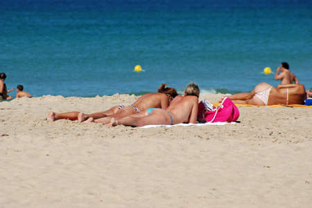 ZAHARA DE LOS ATUNES, SPAIN - SEPTEMBER 14, 2008 - Tourists sunbathing on the beach with the sea to the rear, Zahara de los Atunes, Cadiz Province, Andalusia, Spain, Europe, September 14, 2008.