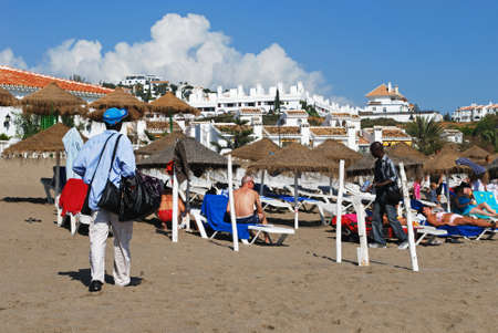 Tourists relaxing on the beach with beach traders showing their goods and apartments to the rear, La Cala de Mijas, Malaga Province, Andalusia, Spain, Western Europe. 新聞圖片