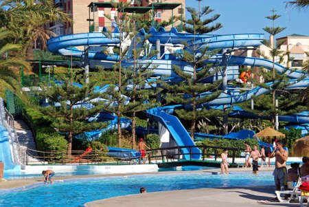 Water slide and pool in the water park with tourists enjoying the setting, Fuengirola, Malaga Province, Andalusia, Spain, Western Europe. Editorial