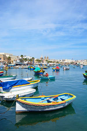 Traditional Maltese Dghajsa fishing boats in the harbour with waterfront buildings to the rear, Marsaxlokk, Malta, Europe.