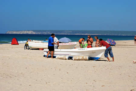 Wooden fishing boat on the beach with tourists enjoying the setting, Zahara de los Atunes, Cadiz Province, Andalusia, Spain, Europe. Editorial