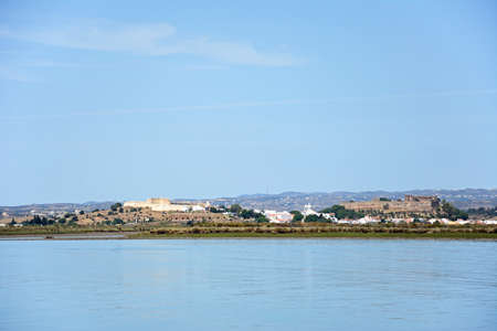 View across the River Guadiana towards the white town and its fort and castle, Castro Marim, Algarve, Portugal, Europe.