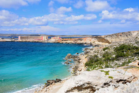 Rocky coastline with hotels to the rear, Paradise Bay, Malta, Europe. 免版税图像