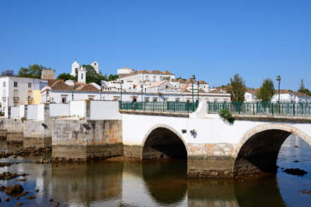 View of the Roman bridge (Ponte Romano) and Gilao river with town buildings to the rear, Tavira, Algarve, Portugal, Europe. 스톡 콘텐츠