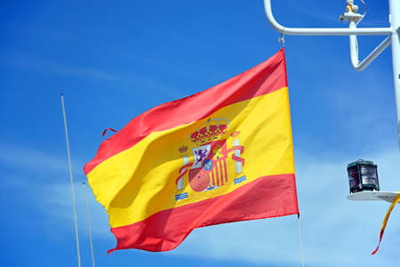 Spanish flag on a fishing boat against a blue sky, Ayamonte, Huelva Province, Andalusia, Spain, Europe. Stock Photo