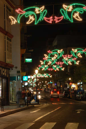 Christmas decorations along a town centre street at night, Fuengirola, Costa del Sol, Malaga Province, Andalucia, Spain.
