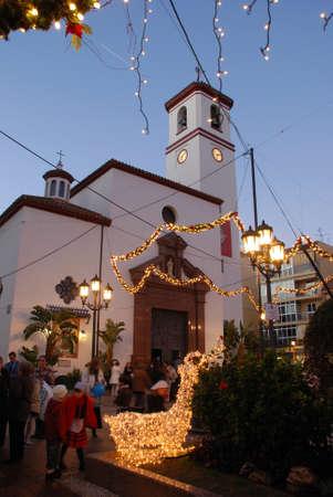 Church (Iglesia de Nuestra Senora de Rosario) in Constitution Square (Plaza de la Constitucion) at dusk with Christmas lights in the foreground, Fuengirola, Costa del Sol, Malaga Province, Andalucia,