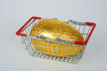Chocolate Easter egg wrapped in gold foil in a shopping basket against a white background, UK. Standard-Bild