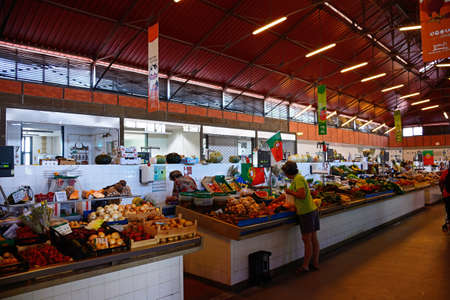 Shoppers looking at the fresh produce for sale in the indoor market, Olhau, Algarve, Portugal, Europe. Editorial