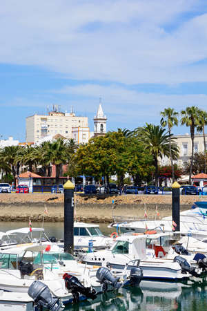 Motor boats moored in the marina (Puerto Ayamonte) with town buildings to the rear, Ayamonte, Huelva Province, Andalucia, Spain, Europe.