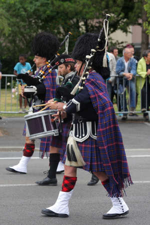 Person dressed in traditional Scottish dress marching for the national day of 14 July commemorating the French Revolution in Saint Quentin. Picardie region of France Editorial