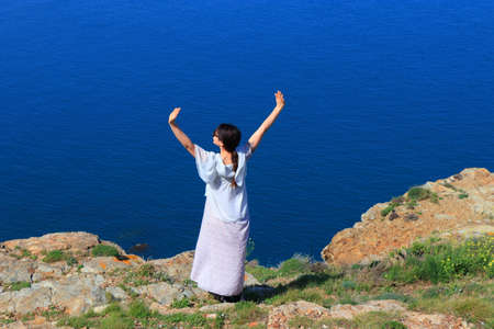 young woman alone raising her arms to the sky in front of the mediterranean sea, Pyrenees orientales in southeren of France