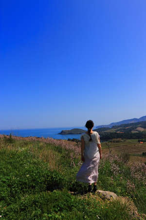 Young woman in dress admiring a Mediterranean landscape, Pyrenees orientales in southern of France