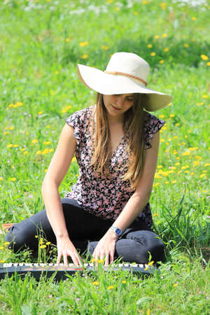 Young and pretty woman with a hat playing synthesizer in a spring meadow