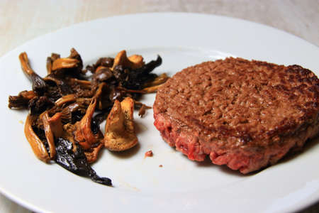 plate of forest mushrooms with a chopped steak
