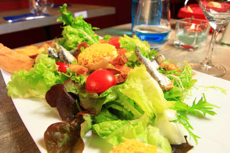 Salad prepared with mimosas eggs and a portion of onion pie in a French restaurant Archivio Fotografico
