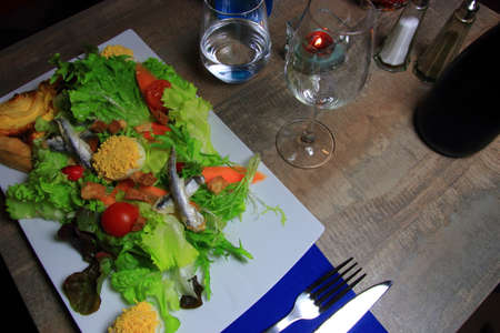 Salad prepared with mimosas eggs and a portion of onion pie on the table of a French restaurant