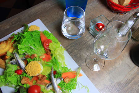 Salad prepared with mimosas eggs and glasses on the table of a French restaurant