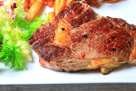 plate of steak with french fries and lettuce salad