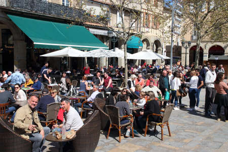 Crowd of people sitting on the terrace of bar at the carnival of Limoux in Aude, Occitanie in the south of France