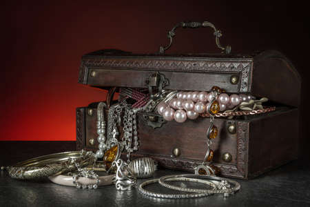 Wooden chest full of jewelry against black and red  background photo