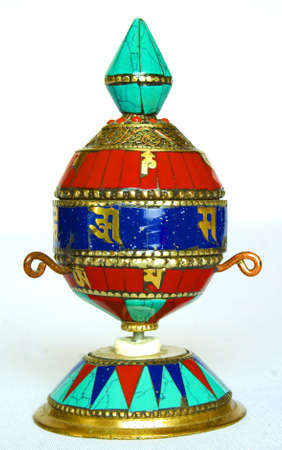 soli: ornate buddist prayer wheel on a light background