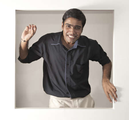 biege: young indian man looking happy in a black short biege pants looking out of a window Stock Photo