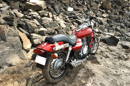 red motorcyle sandy beach rocky embankment landscape copy space photo