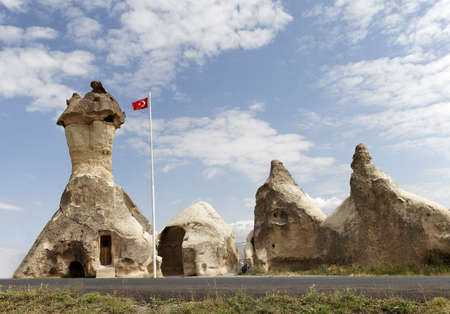 Church formed from limestone caves, Coppadocia, Turkey. Bus stop, turkish flag