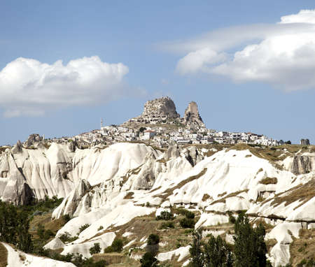 Uchisar on top of limestone terrain viewd from Goreme, blue sky with white clouds photo