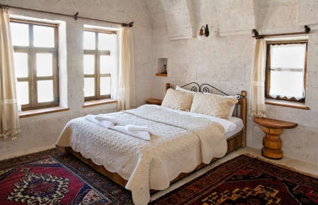 interior detailing of bedroom under the limestone arches, white detailed bedspread and cushions furniture, woven mats and net curtains. Landscape, copy space and crop area Stock Photo