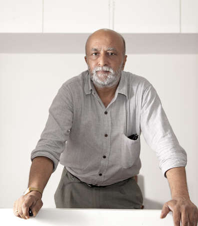 receeding indian man, beard and western dress looking straight into the camera, hold a remote switch and having sunglasses in his rolled up long sleeve shirt photo