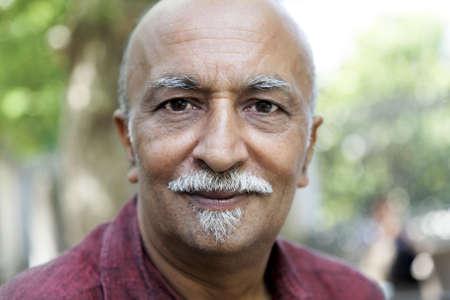 faint smile on an Indian man in western attire burgundy shirt, balding, van dyke beard, horizontal, crop space and copy space Stock Photo - 10160392