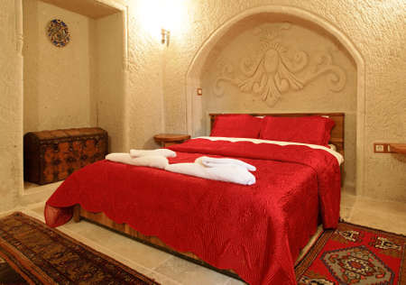 architectural detailing: interior architectural detail of bedroom with alcove and archway with detailing, bed cover in embroidered bright red bedspread and pillow cases, treasure chest shipping trunk, woven mats and wall light. Landscape with crop area and copy space.