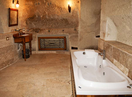 architectural detailing: layout of bathroom with marble tiling showing bath tub, dresser still wash basin, wall lights, radiator and alcoves. Horizontal, copy area and crop space