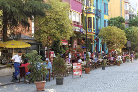 Istanbul, Turkey, June 2011 - colourful street landscape where brightly colored restaurants lay outdoor tables for diners with vivid painted building exteriors Editorial